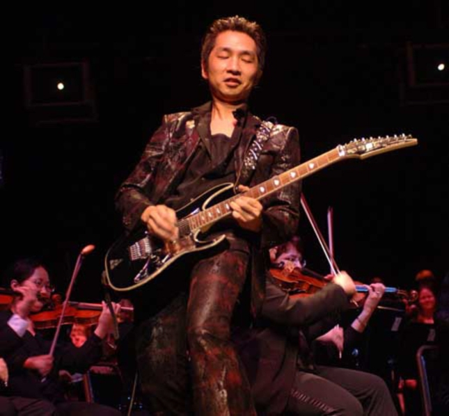 Akira Yamaoka photo, playing guitar at orchestra.